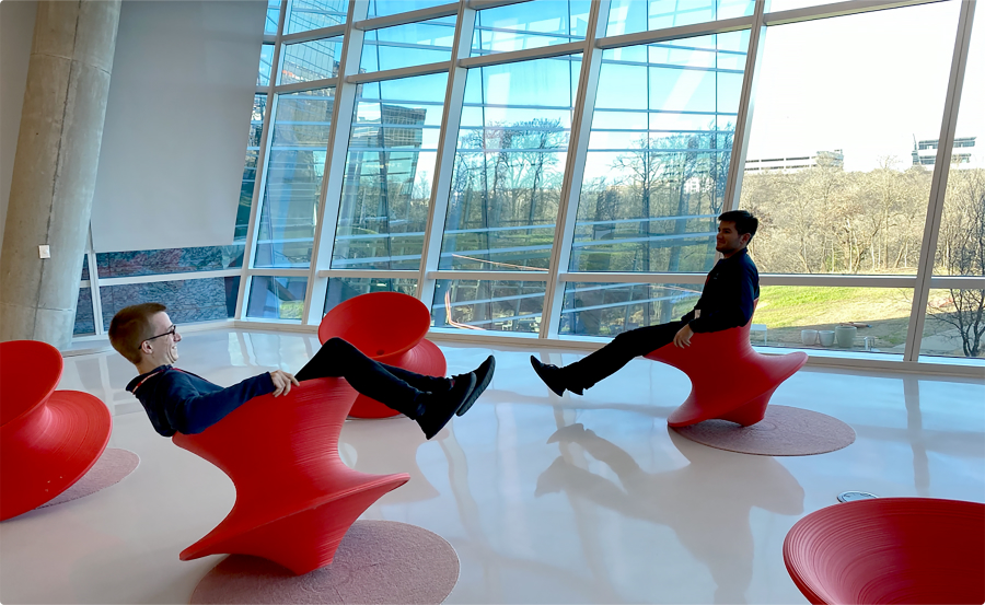 Two men sitting on spinning top red chairs.