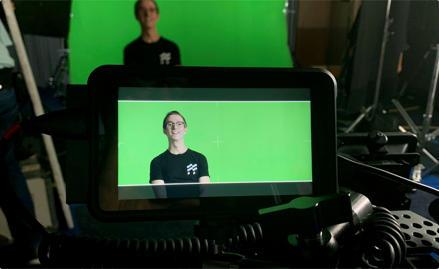 Man with Duffel tee-shirt in front of green screen being recorded by professional camera.